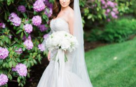 A bride by pink flowers - Photo by Lisa Rigby